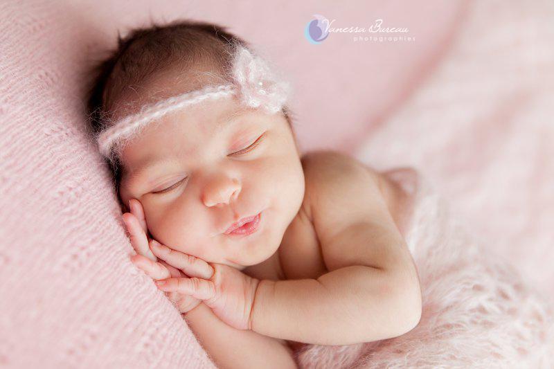 Nouveau-né sur fond rose, petit moue mignonne