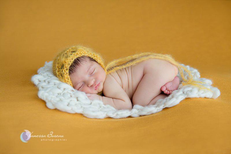 Nouveau-né, photographe Dijon, bébé sur le ventre, plaid jaune moutarde et bonnet assorti