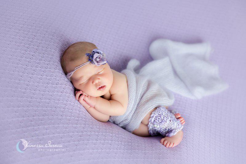 Nouveau-né, photographe Dijon, allongée sur le côté avec fleur violette
